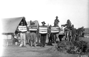 Four soldiers display fresh baked loaves of bread in front of the camp bakery, Fort Logan, Colorado. A campfire ring stacked high with rocks is outside the bakers tent. World War I. 1917. (George L. Beam/Denver Public Library/Western History Collection/GB-7584)  denver public library; dpl; archive; archival; world war I; military; george l beam; denverite;