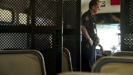 Deputy Moore of the Court Services Division stands inside of a Denver Sheriff's Department prisoner transport bus. (Kevin J. Beaty/Denverite)  police; denver; colorado; kevinjbeaty; denverite