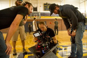 """Colorado-based first assistant camera operator Calvin Sneed (center) adjusts a focus ring between takes during the production of """"Amateur,"""" a Netflix feature film being shot at Regis University. (Kevin J. Beaty/Denverite)filmmaking; set; film; tv; production; kevinjbeaty; denver; denverite; regis university; colorado;"""