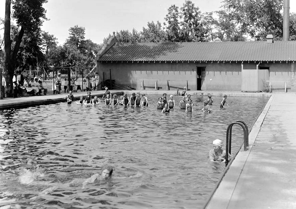 A group of girls stand in the shallow end of the Lincoln Park pool in the Lincoln Park neighborhood of Denver, Colorado. Women and children spectators are outside the fence. The bath house is in the distance. Between 1920 and 1940. (Denver Public Library/Western History Collection/X-27633)  summer; pool; historic; denver public library; dpl; archive; archival; denverite