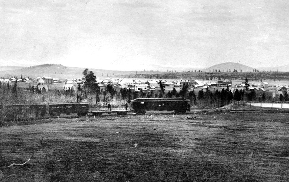Panoramic view of the town of Fairplay, Colorado, in Park County. In the foreground, two men stand on a flatbed car attached to other cars of the Denver South Park & Pacific Railroad. Between 1860 and 1880. (Denver Public Library/Western History Collection/X-8327)  south park; fairplay; history; historic; denver public library; dpl; archive; archival; denverite;