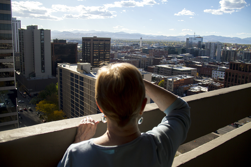 Susan Dean peeks over the railing of her apartment's top story. (Kevin J. Beaty/Denverite)  susan dean; oped; kevinjbeaty; denverite; denver; colorado; kevinjbeaty;