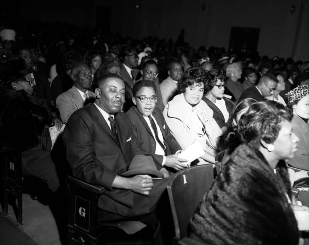 """View of a Links Club function. An African American family sit in a theater in Denver, Colorado. A man, woman and young boy are seated in row """"G"""" in the crowded audience. The man holds a hat on his lap. Between 1950 and 1960. (Burnis McCloud/Denver Public Library/Western History Collection/MCD-185)  five points; historic; denver public library; dpl; archive; archival; denverite"""
