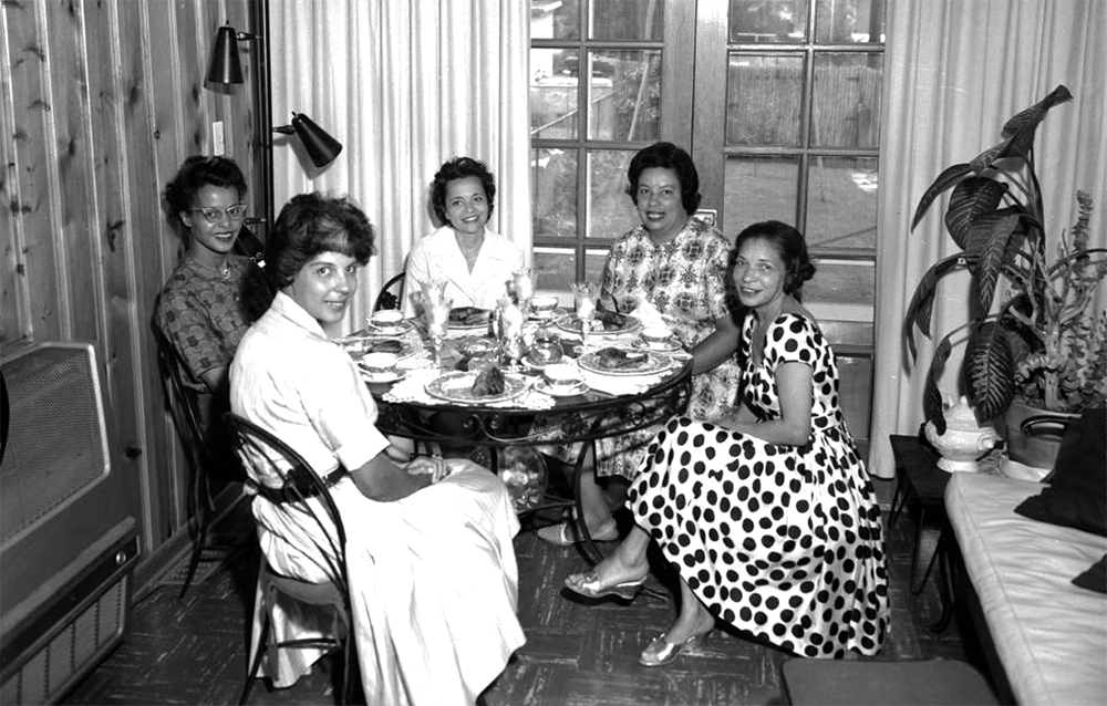 View of an Owlettes Club function. A group of African American (Black) women sit at a table in a dining room in Denver, Colorado. One woman wears a bold polka dot dress with a full skirt and another wears a short sleeve, shirtwaist style dress with a full skirt. The table is set and a piece of chicken sits on each plate. Between 1950 and 1960. (Burnis McCloud/Denver Public Library/Western History Collection/MCD-202)  five points; historic; denver public library; dpl; archive; archival; denverite