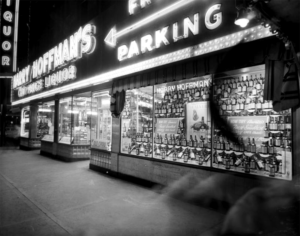 """Night view of Harry Hoffman's Cut Price Liquor store at Curtis and 18th (Eighteenth) Streets in Denver, Colorado. Windows display bottles of Calvert whiskey; neon signs read """"Harry Hoffman's"""" """"Liquor"""" and """"Free Parking."""" Between 1950 and 1960. (Burnis McCloud/Denver Public Library/Western History Collection/MCD-3)  five points; historic; denver public library; dpl; archive; archival; denverite"""