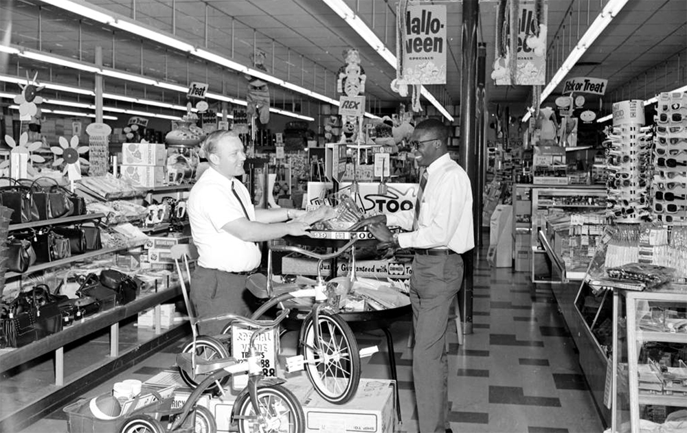 Two men, one is African American, stand inside a Duckwall variety store. Sunglasses, tricycles, handbags, irons, lamps are all for sale. between 1950 and 1970. (Burnis McCloud/Denver Public Library/Western History Collection/MCD-92)  five points; historic; denver public library; dpl; archive; archival; denverite