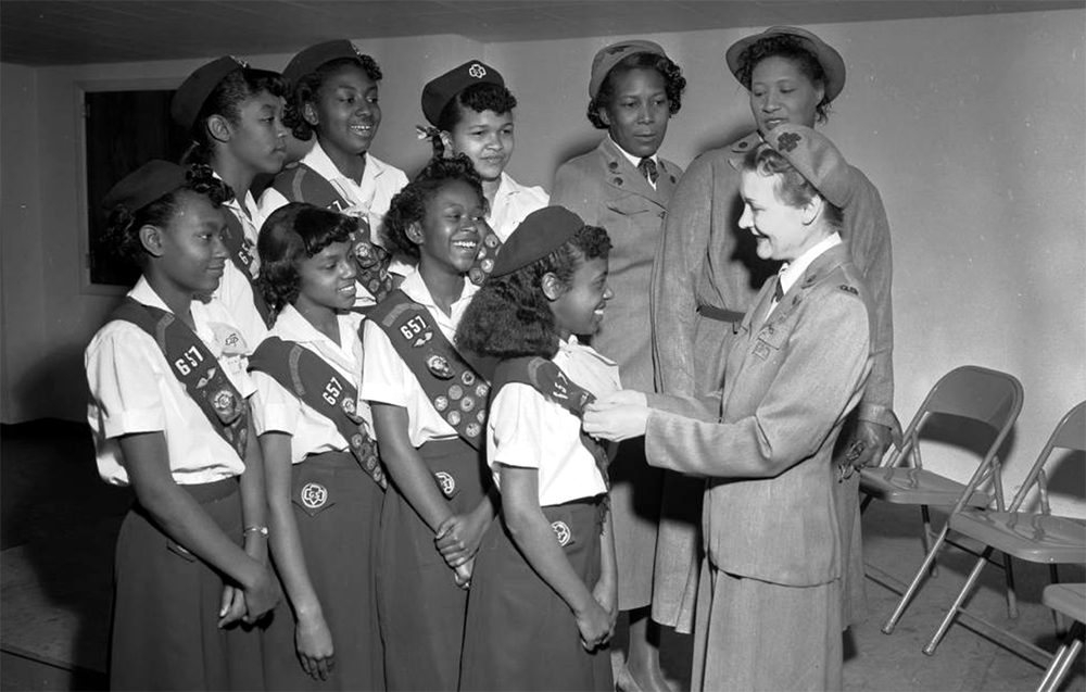 """A group of African American (Black) girls and women in Girl Scout uniforms stand in formation to receive badges. A white woman in a dress uniform pins a badge reading: """"Be Prepared"""" on a young girls sash. Other badges indicate that the girls belong to Troop 657, Metro Denver. Between 1940 and 1950. (Burnis McCloud/Denver Public Library/Western History Collection/MCD-160)  five points; historic; denver public library; dpl; archive; archival; denverite"""