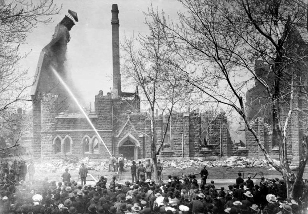 Firemen aim a jet of water at a collapsing chimney amid the ruins of the 23rd Avenue Presbyterian Church after the fire that destroyed the 1892 building in 1906. A crowd of spectators look at the remains of the stone building. April 16, 1906. (Harry Mellon Rhoads/Denver Public Library/Western History Collection/Rh-5862)  historic; denver public library; dpl; archive; archival; denverite