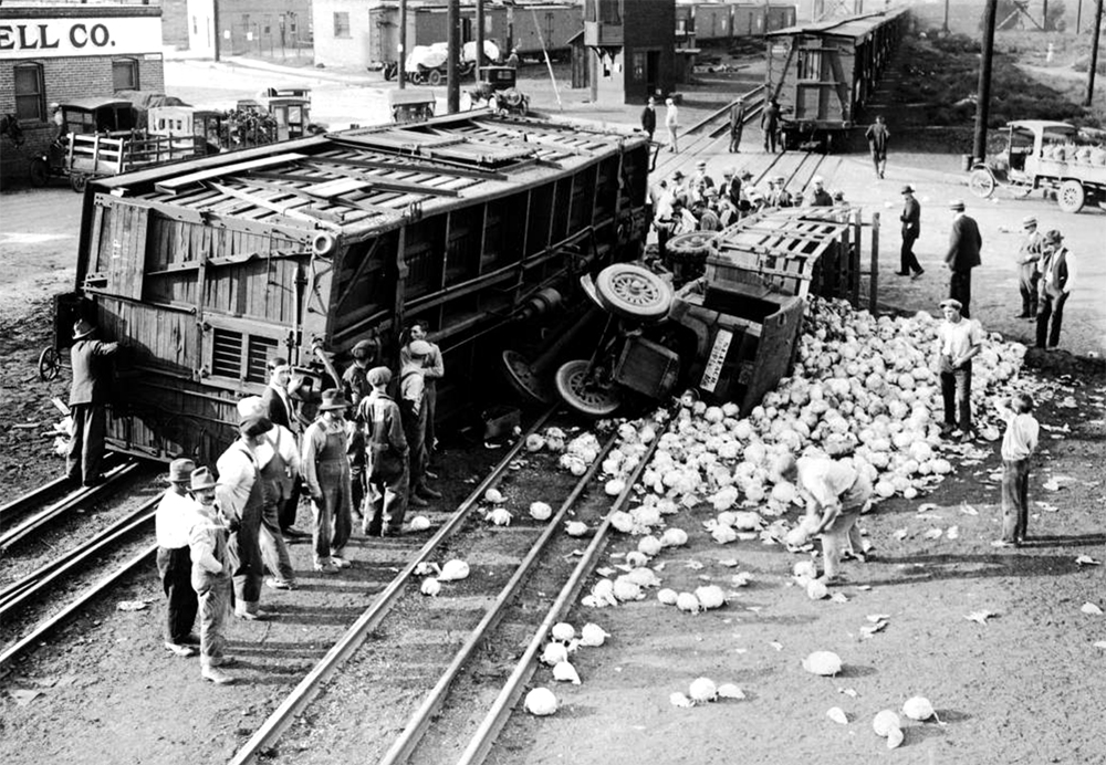 """""""A relatively harmless cabbage accident some years back."""" A crowd of people are gathered around a spilled truckload of cabbage and a derailed railroad train car in Denver, Colorado. Between 1920 and 1930. (Harry Mellon Rhoads/Denver Public Library/Western History Collection/Rh-5916)  historic; denver public library; dpl; archive; archival; denverite"""