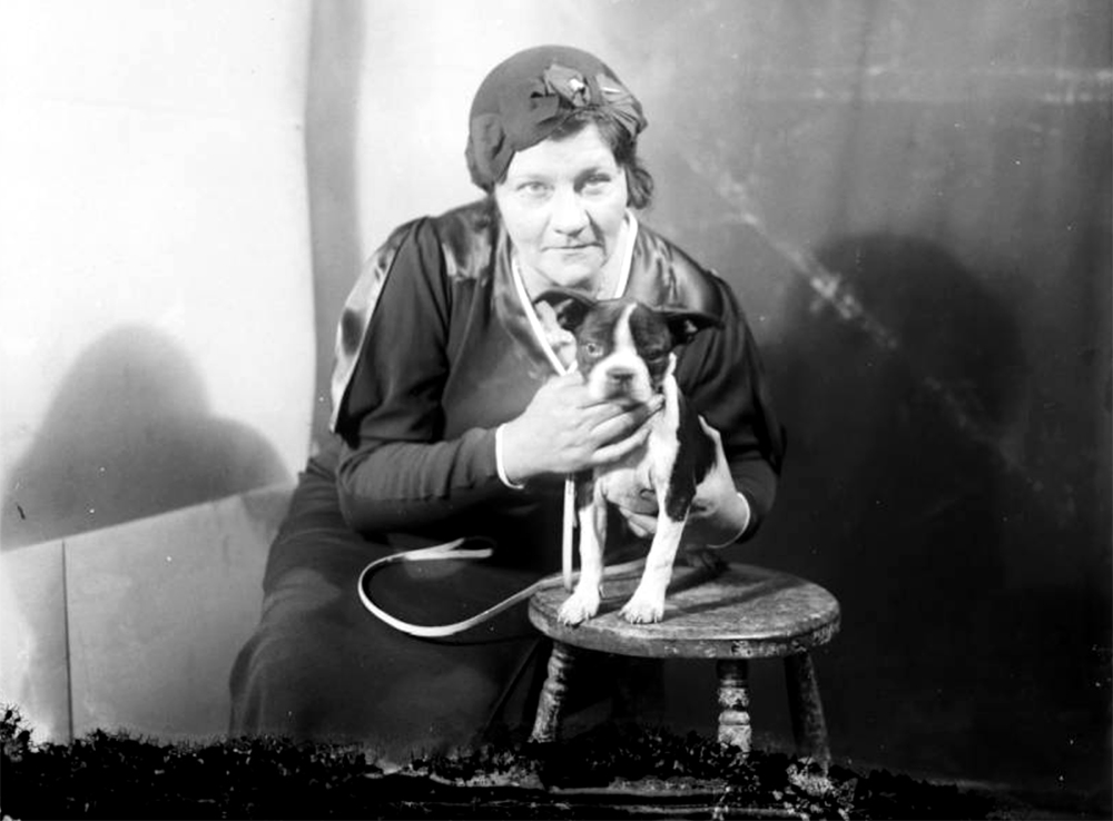 A woman wearing a flowered cloche hat poses with a French bulldog. Between 1920 and 1930. (Harry Mellon Rhoads/Denver Public Library/Western History Collection/Rh-1540)  historic; denver public library; dpl; archive; archival; denverite