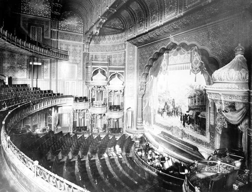 """Interior view of Broadway Theatre located in Metropole Hotel on Broadway, Denver, Colorado; shows balcony, private box seats, orchestra pit, stage, and scenery curtain from """"A glimpse of India;"""" theater opened in 1890. Circa 1900. (Louis Charles McClure/Denver Public Library/Western History Collection/MCC-6)  historic; denver public library; dpl; archive; archival; denverite"""