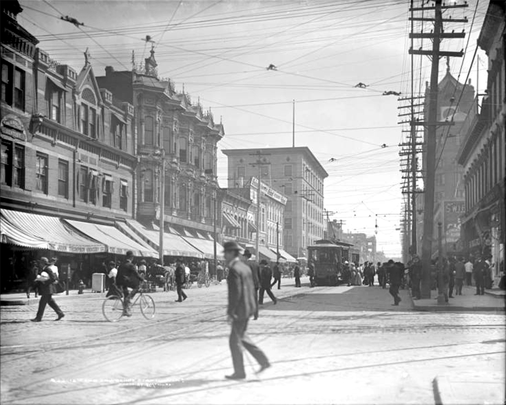 View of 15th (Fifteenth) and Lawrence Streets. Businesses include John Thompson Grocery Company, Dr. Grant Seely (dentist), Grand Butchers, Tabor Opera House, and rooms for rent. Between 1898 and 1915. (Louis Charles McClure/Denver Public Library/Western History Collection/MCC-593)  historic; denver public library; dpl; archive; archival; denverite