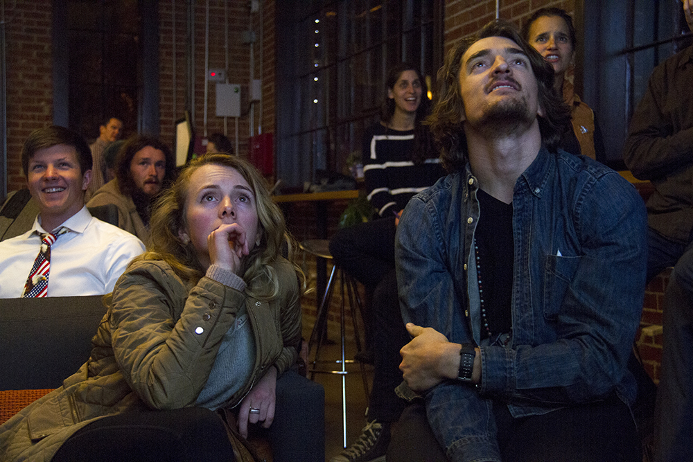 Hannah Merten and Mike Schutte watch results roll in during the Denverite Election Party, Nov. 8, 2016. (Kevin J. Beaty/Denverite)  election; vote; voting; copolitics; politics; election party; kevinjbeaty; denver; denverite; colorado; galvanize;