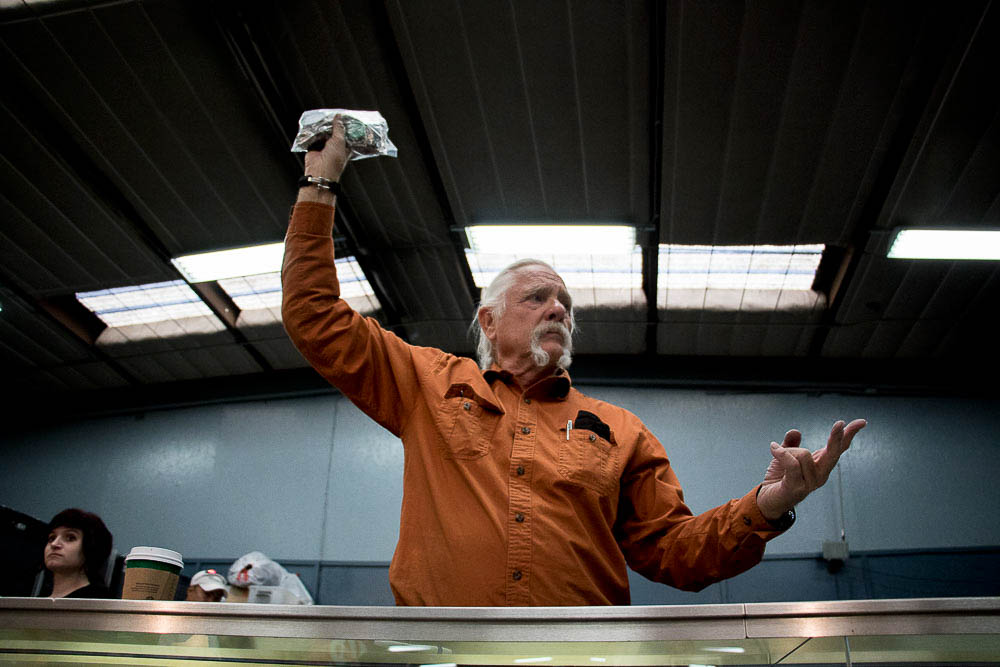 Randy Wilson holds up a bag of jewelry at Dickensheet and Associate's auction. (Chloe Aiello/Denverite)