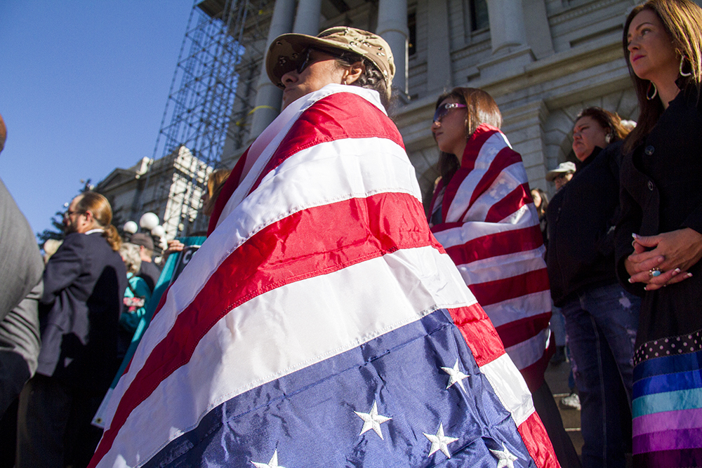 Draped in a flag, Nancy Rae Clark stands on the Capitol steps during a rally against Donald Trump in reaction to his election just days prior. Nov. 10, 2016. (Kevin J. Beaty/Denverite)  rally; protest; trump; politics; copolitics; capitol; denver; denverite; colorado; kevinjbeaty; election;