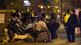 "About a hundred or so people hang out on the corner of Lawrence and Broadway just one day after so-called ""homeless sweeps"" by the city. (Kevin J. Beaty/Denverite)  camping ban; right to rest; denver rescue mission; denver; colorado; homeless; denverite; kevinjbeaty;"