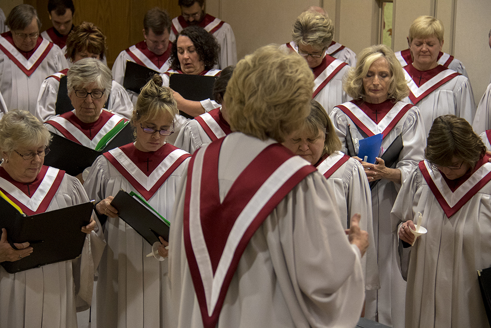 Music Director Judith Mitchell leads the choir in a prayer for a member whose daughter has just passed away. Christmas Eve at Trinity United Methodist Church, 2016. (Kevin J.Beaty/Denverite)  christmas eve; holidays; downtown; kevinjbeaty; denver; denverite; colorado;