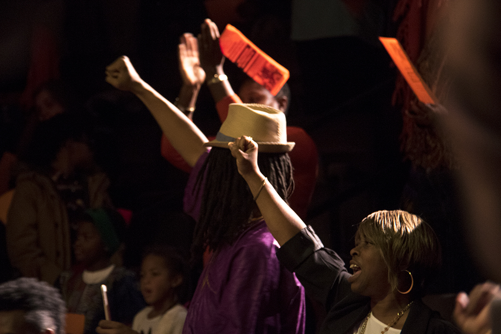 People in the crowd raise their fists. The first night of Kwanzaa at the Cleo Parker Robinson Dance Theatre, Dec. 26, 2016. (Kevin J. Beaty/Denverite)  kwanzaa; Cleo Parker Robinson Dance Theatre; holidays; denver; denverite; kevinjbeaty; colorado; five points;