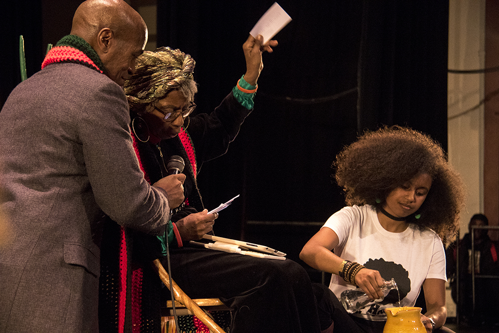 Ms. Isetta Crawford Rawls reads the names of people lost this year, as written in by the audience. The first night of Kwanzaa at the Cleo Parker Robinson Dance Theatre, Dec. 26, 2016. (Kevin J. Beaty/Denverite)  kwanzaa; Cleo Parker Robinson Dance Theatre; holidays; denver; denverite; kevinjbeaty; colorado; five points;