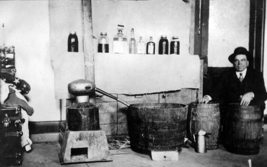 A man sits near a moonshine still in Anton Herbenich's home in Pueblo, Colorado. The still consists of a covered metal container, pipes, and barrels. Bottles and jars of liquor are arranged on a counter. (Denver Public Library/Western History Collection/X-29651)