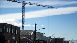 A crane looms over Brighton Boulevard, across the street from Rhinoceropolis and GLOB. (Kevin J. Beaty/Denverite)