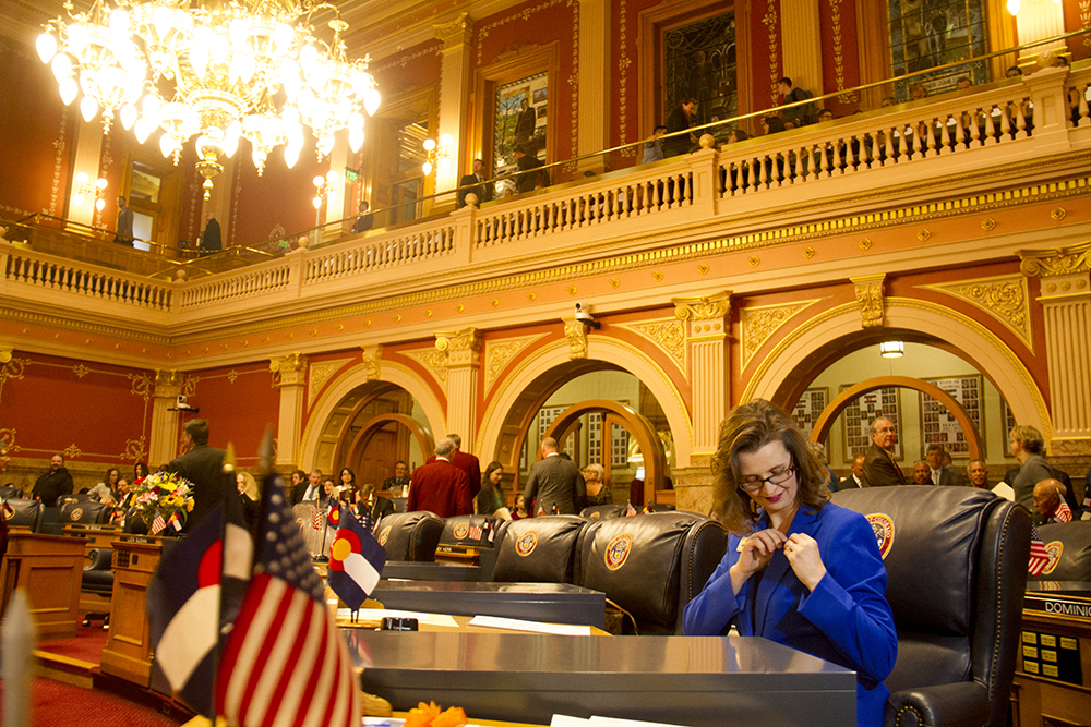 District 19 Senator Rachel Zenzinger applies a pin to her lapel on the first day of the Colorado state legislative session. Jan 11, 2017. (Kevin J. Beaty/Denverite)  legislature; copolitics; politics; legislative session; capitol; kevinjbeaty; denver; denverite; colorado;