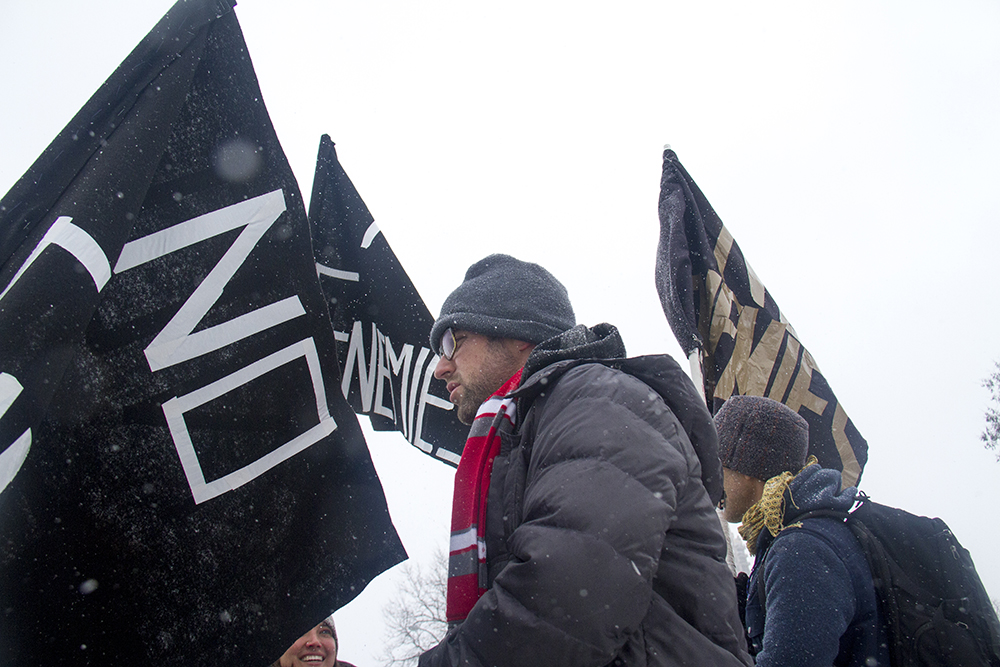 "Jamie ""Jonny 5"" Laurie stands amongst flags reading ""No Enemies,"" the name of the movement he co-founded and (also the forthcoming Flobots album) that tries to realize music as an avenue to achieve social change. Jan. 16, 2017. (Kevin J. Beaty/Denverite)  mlk; marade; martin luther king jr; city park; denver; colorado; kevinjbeaty;"