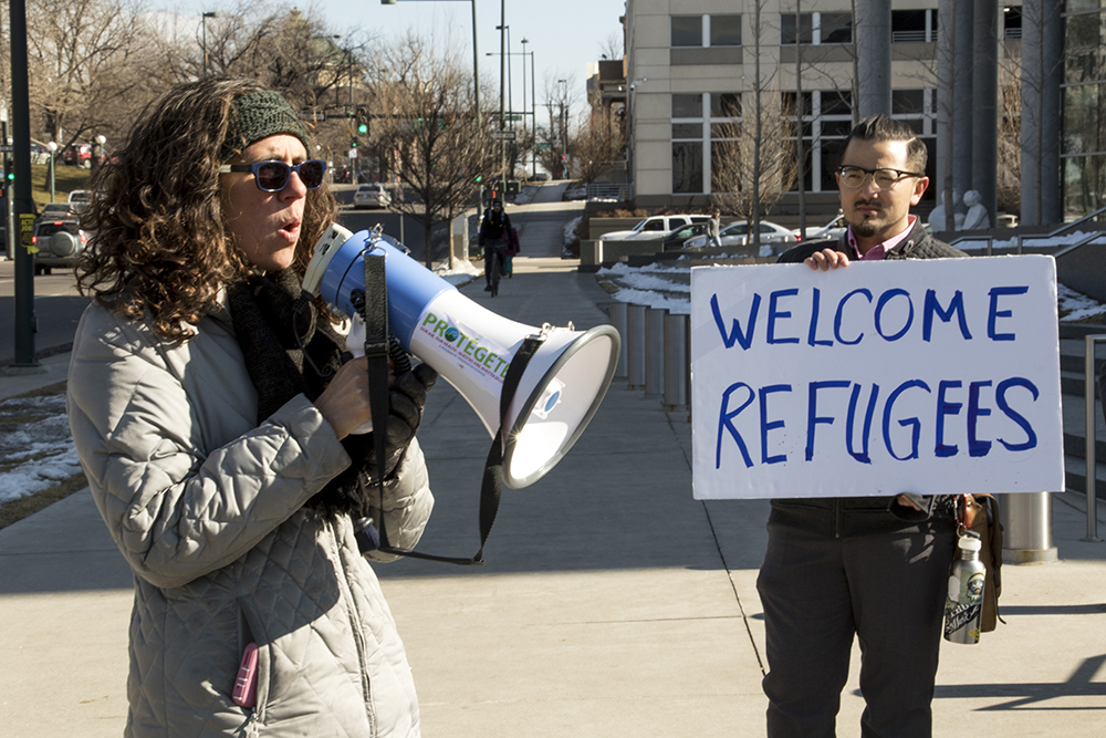 Gabriela Flora of American Friends Service Committee leads a chant to support SB251 and protest President Trump's executive orders on immigration. (Chloe Aiello/Denverite)  donald trump; sb251; immigration; denver; colorado; civic center park; denverite; chloe aiello; protest; vigil