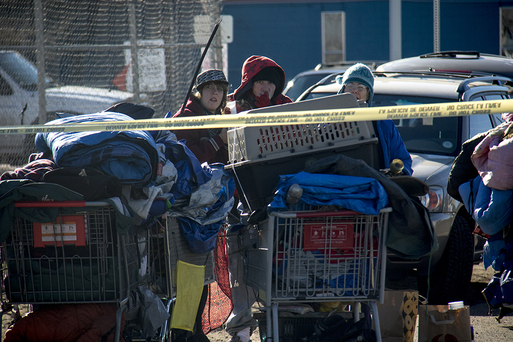 """Amanda Berry (left) watches as city workers """"sweep"""" a homeless encampments at Denargo and Delgany Streets where she was staying for two months, Jan. 26, 2016. (Kevin J. Beaty/Denverite)  homelessness; sweeps; right to rest; denver; colorado; kevinjbeaty; denverite;"""