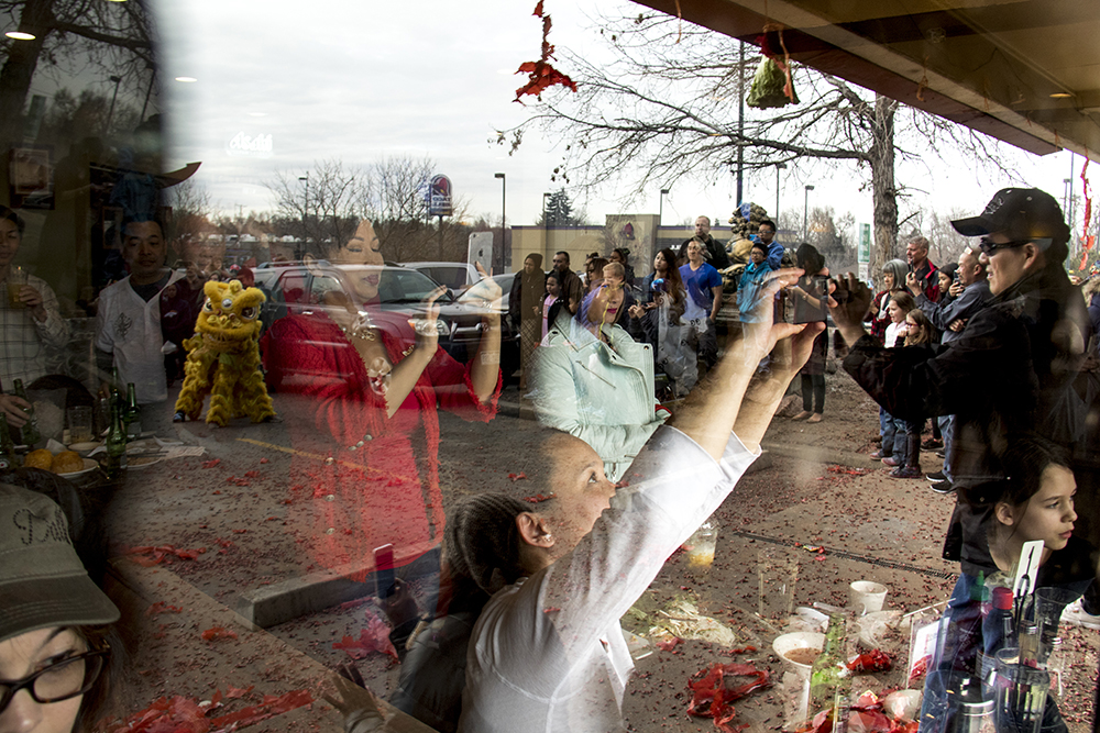 Spectators inside and outside of Saigon Bowl Restaurant watch the Nguyen Thieu Buddhist Youth Group perform during Chinese New Year, Jan. 29. 2017. (Kevin J. Beaty/Denverite)  chinese new year; federal boulevard; westwood; denver; kevinjbeaty; denverite; colorado;