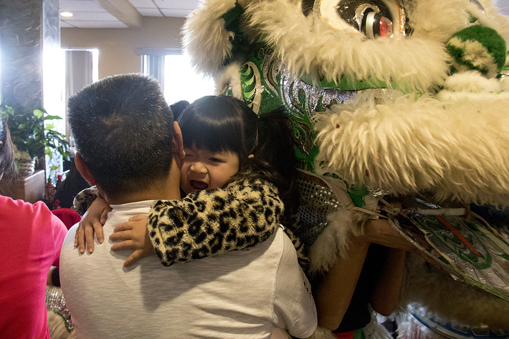 Nguyen Thieu Buddhist Youth Group performers dressed as a lion scares Kayla Trang, 3, during Chinese New Year, Jan. 29. 2017. (Kevin J. Beaty/Denverite)  chinese new year; federal boulevard; westwood; denver; kevinjbeaty; denverite; colorado;