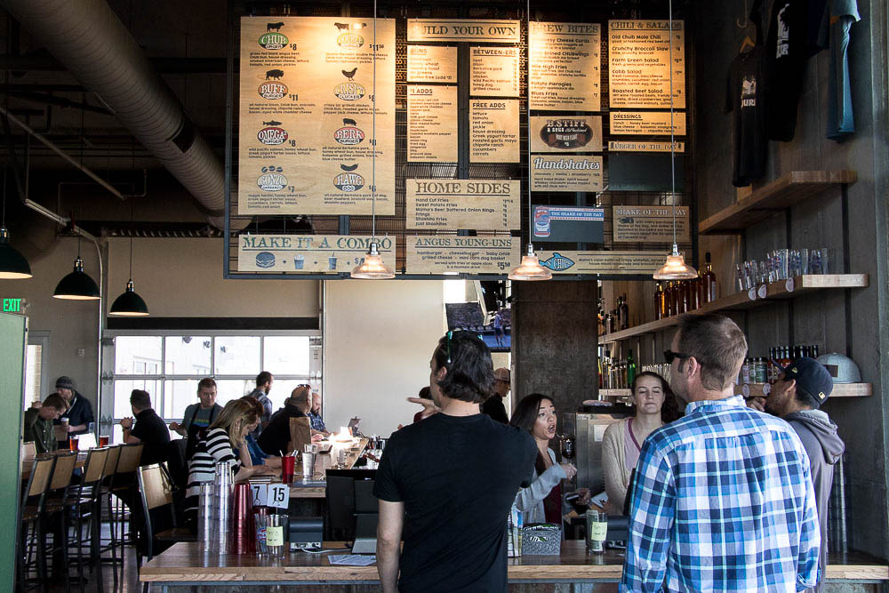 Will Self and Donny Schmidt examine the menu at Oskar Blues Fooderies' CHUBurger on opening day. (Chloe Aiello/Denverite)