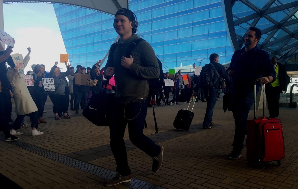 A man walks past protesters at Denver International Airport on Sunday Jan. 29, 2017.