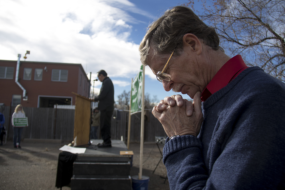"""Pro-life activist Tom Uebbing bows his head as Father John Paul Leyba leads a prayer. A """"Defund Planned Parenthood"""" Rally outside Planned Parenthood of the Rockies, Feb. 11, 2017. (Kevin J. Beaty/Denverite)  abortion; pro life; planned parenthood; denver; colorado; kevinjbeaty; denverite; copolitics; politics;"""