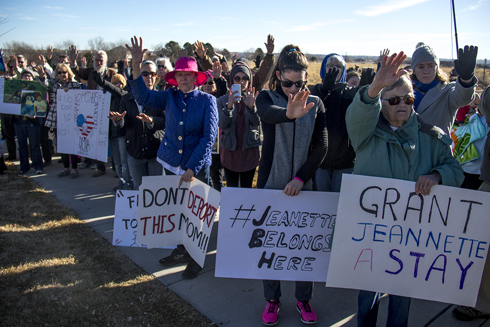 Jeanette Vizguerra's supporters raise their hands in prayer outside of the U.S. Immigration and Customs Enforcement local headquarters in Centennial, Feb. 15, 2017. (Kevin J. Beaty/Denverite)  jeanette vizguerra; immigration; undocumented; deportation; sanctuary; denver; colorado; kevinjbeaty; denverite;