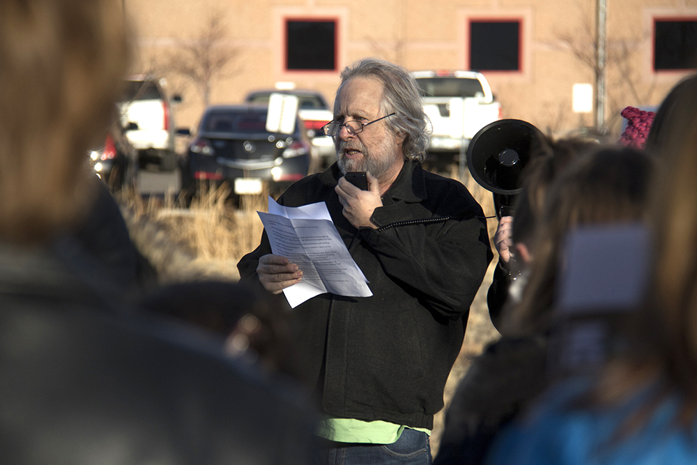 Alan Rosenfeld reads a quote by Rabbi Joachim Prinz, who escaped Nazism in Germany during WWII, spoke alongside Dr. Martin Luther King Jr. and became a zionist leader. A rally outside of the GEO private immigrant detention facility. (Kevin J. Beaty/Denverite)  ICE; immigration; deportation; aurora; protest; rally; denver; colorado; kevinjbeaty; denverite