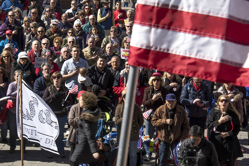 The crowd covers hearts during the pledge of allegiance. A rally in support of President Trump, Feb. 27, 2017. (Kevin J. Beaty/Denverite)  copolitics; politics; trump; rally; protest; capitol; denver; colorado; denverite; kevinjbeaty
