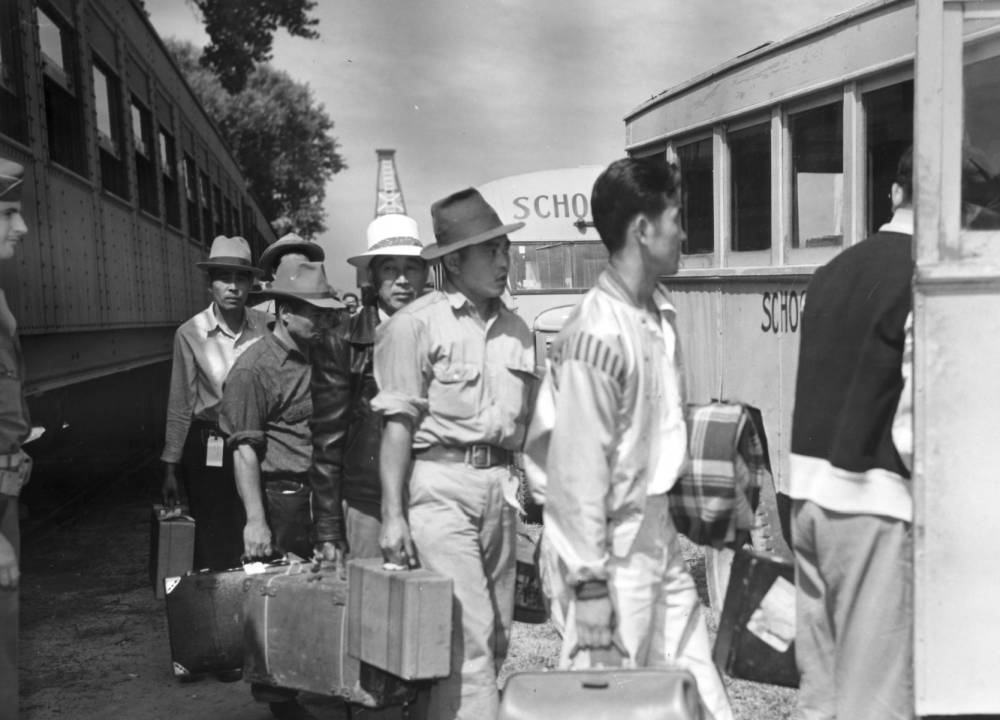 Japanese men arrive from the Merced Assembly Center, California, by train, carrying suitcases and boarding school buses on their way to the Camp Amache internment zone in Colorado, Aug. 28, 1942. (Tom Parker/War Relocation Authority/Western History and Genealogy Department/Denver Public Library)