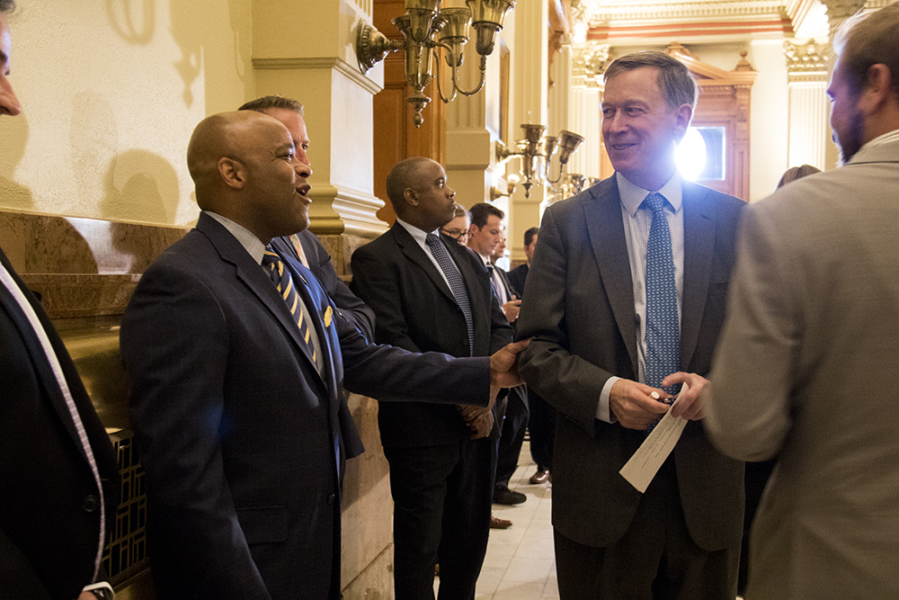 Governor John Hickenlooper chats with Mayor Michael Hancock at a press conference on a compromise bill to address issues surrounding construction defects, April 19, 2017. (Kevin J. Beaty/Denverite)  denver; denverite; kevinjbeaty; colorado;