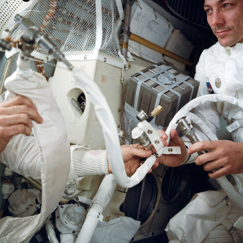 "The late Colorado astronaut John L. Swigert, at right, with the ""mailbox"" rig improvised to adapt the Command Module's square carbon dioxide scrubber cartridges to fit the Lunar Module, which took a round cartridge. (BASA)"