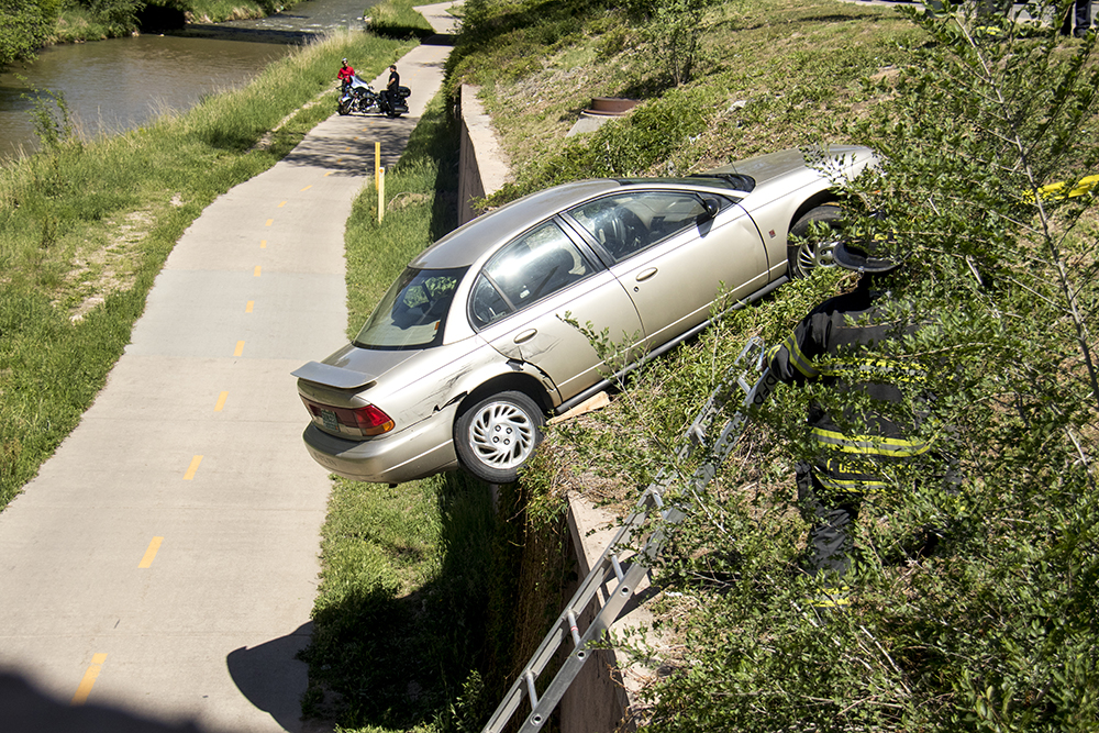 A car that has been spun off the road and almost into the Cherry Creek Trail near Speer Boulevard and 8th Avenue. (Kevin J. Beaty/Denverite)  accident; car crash; cherry creek trail; speer boulevard; kevinjbeaty; denver; colorado; denverite;