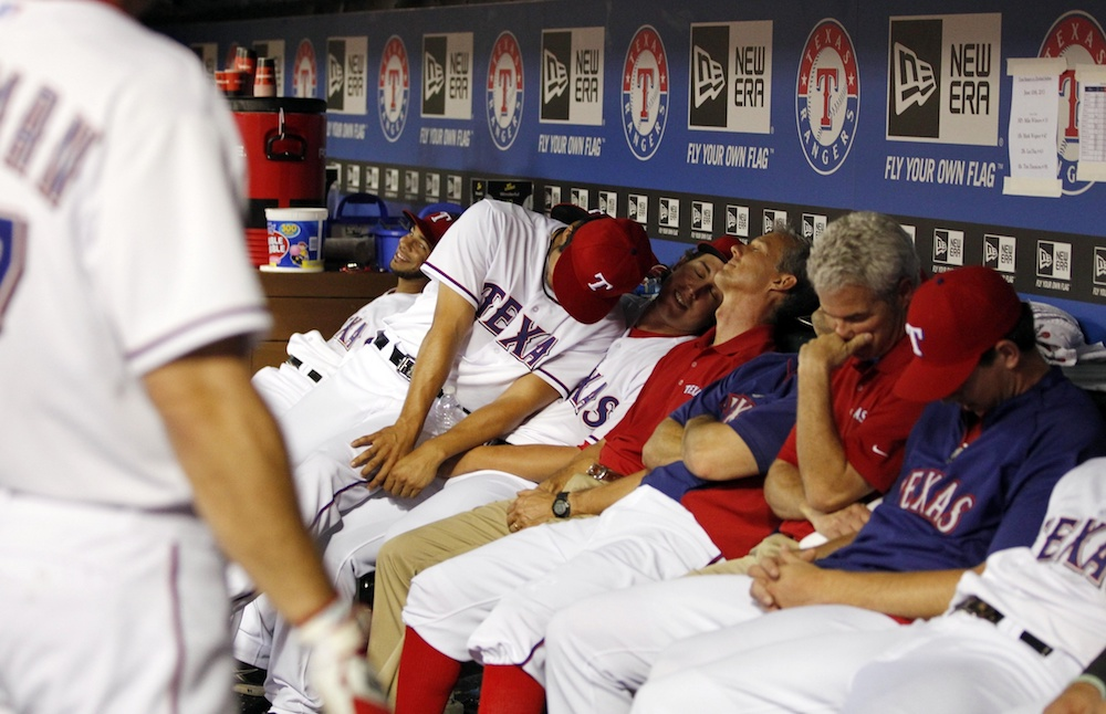 """Rangers players """"sleep"""" in the dugout in a 2013 game. (Tim Heitman/USA Today Sports)"""
