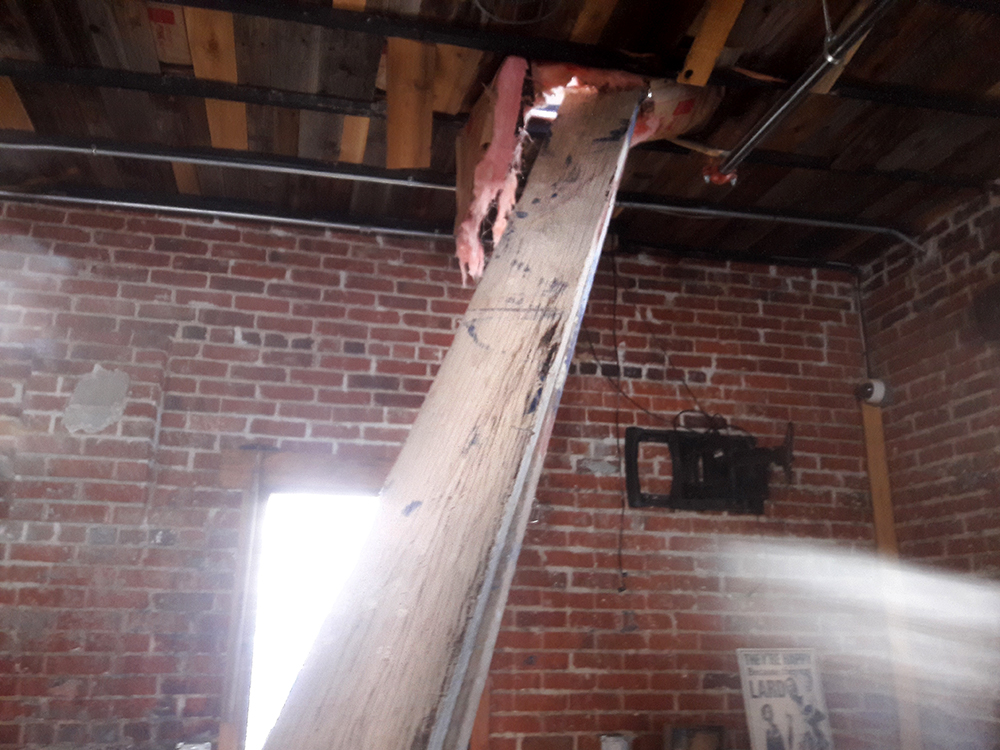 A wooden board through the roof of The Grateful Gnome in Denver's Berkeley neighborhood, June 13, 2017. (Adrian D. Garcia/Denverite)