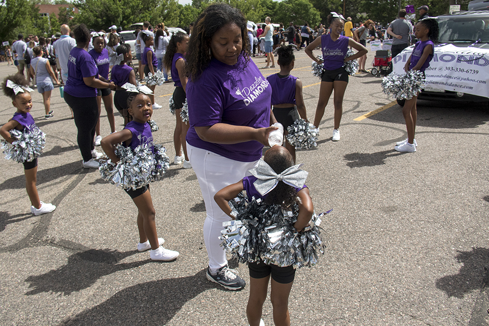 Dazzling Diamonds Coach Amber Adams feeds water to 5 year old Jahnayla so she doesn't mess up her makeup. The Juneteenth parade in Five Points, June 17, 2017. (Kevin J. Beaty/Denverite)