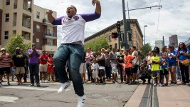 Danny Perkins gets airborn as the Omega Psi Phi Fraternity crosses Welton Street. The Juneteenth parade in Five Points, June 17, 2017. (Kevin J. Beaty/Denverite)  juneteenth; five points; black history; kevinjbeaty; denver; colorado; denverite; street fair; festival; welton street;