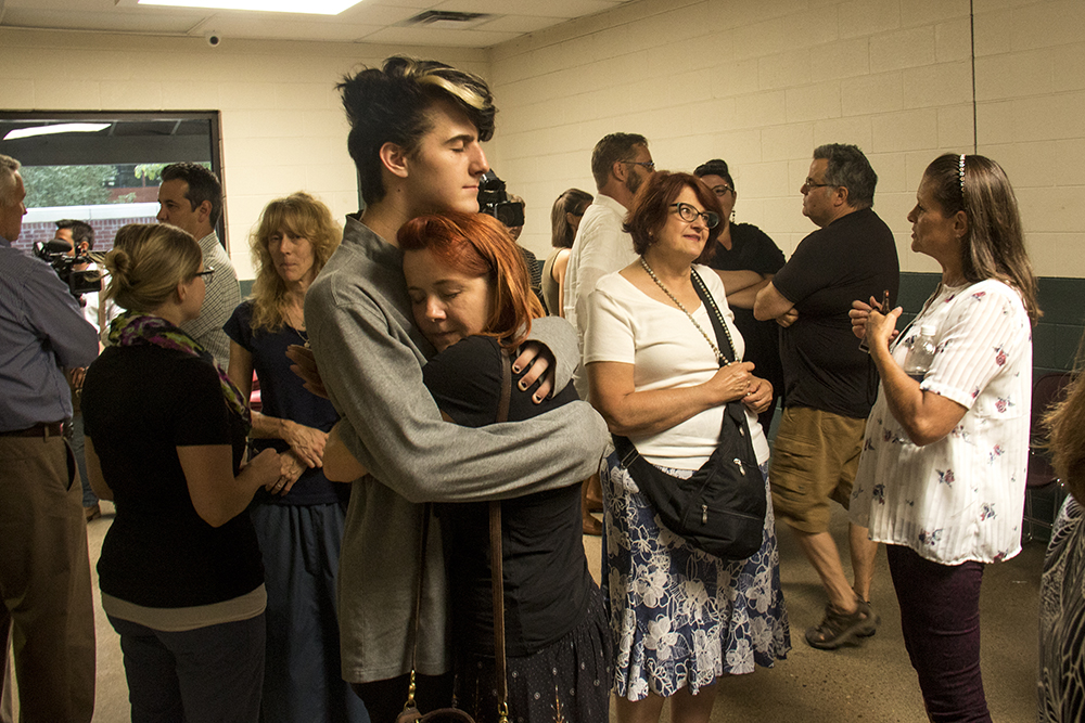 Aidan Brown hugs his mom, Linda. A memorial service for James Farmer Jr. at the St. Francis Center, June 27, 2017. (Kevin J. Beaty/Denverite)  denver; colorado; james farmer jr.; st. francis center; homeless; funeral; kevinjbeaty;
