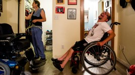 Aaron Walbert and his caretaker, Jennifer Hill, in his room, July 10, 2017. (Kevin J. Beaty/Denverite)  denverite; aaron walbert; denver; colorado; capitol hill; kevinjbeaty;