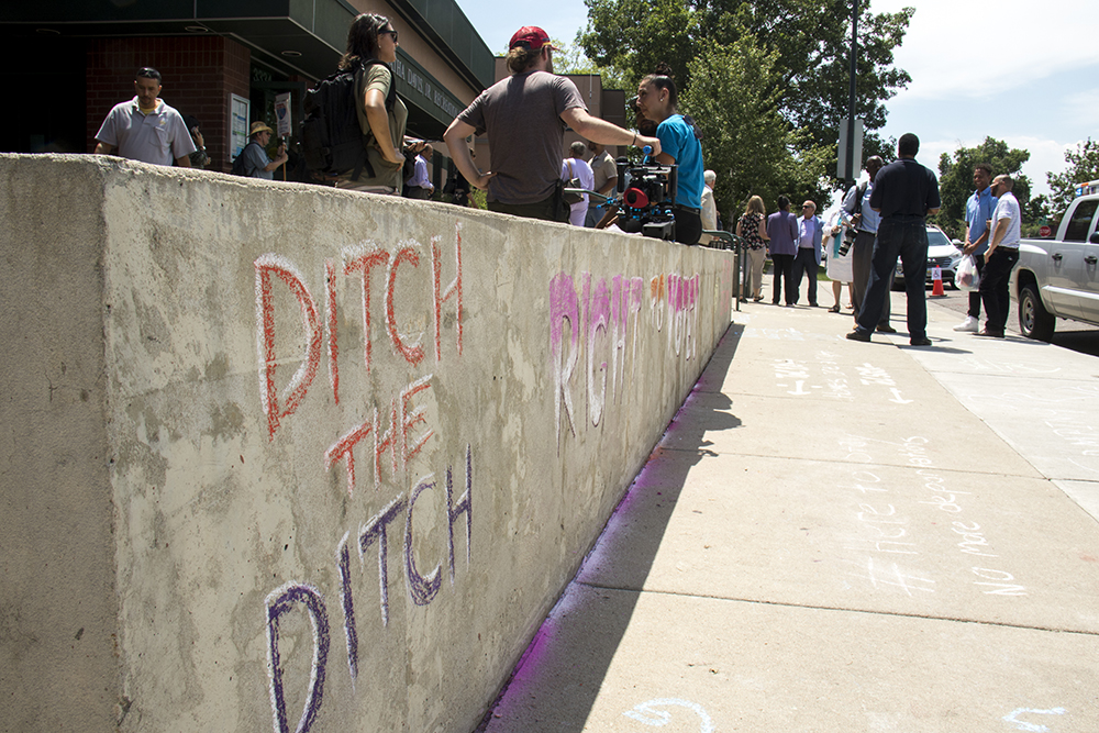 Anti-I-70 activists used chalk to express their point outside of Mayor Hancock's State of the City address, July 10, 2017. (Kevin J. Beaty/Denverite)  state of the city; mayor michael hancock; northeast park hill; denver; denverite; colorado