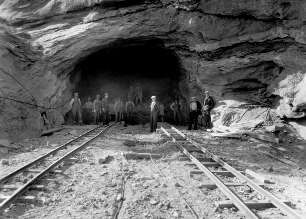 Laborers pose near ore cars and on stone rubble, in the entrance to a road tunnel under construction, in Red Rocks Park, a Denver Mountain Park near Morrison in Jefferson County, Colorado. (Denver Public Library/Western History Collection/Z-8888)  red rocks; civilian conservation corps; archive; denver; colorado; kevinjbeaty;