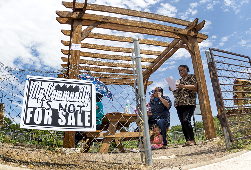 Raymunda Carreón and Ray G. stand inside the community garden at Focus Points. Members of the Globeville, Elyria-Swansea Coalition for Health and Housing Justice call for the creation of a community land trust, July 18, 2017. (Kevin J. Beaty/Denverite)  denver; denverite; kevinjbeaty; colorado; elyria swansea; globeville; focus points; gentrification;